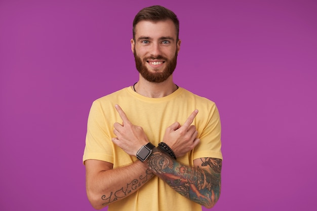 Cheerful pretty blue-eyed bearded male with tattooes wearing casual clothes and fitness watch posing on purple, with charming smile and keeping arms crossed