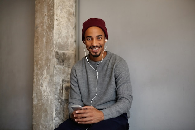 Веселый симпатичный темнокожий парень с карими глазами с бородой слушает музыку со смартфоном и наушниками в ожидании кого-то, глядя с широкой очаровательной улыбкой