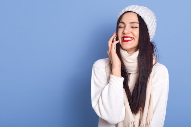 Cheerful pretty brunette girl talking on phone and laughing carefree, holding smartphone near ear