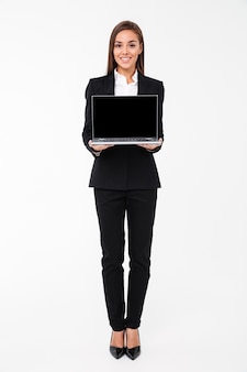Cheerful pretty businesswoman showing display of laptop computer