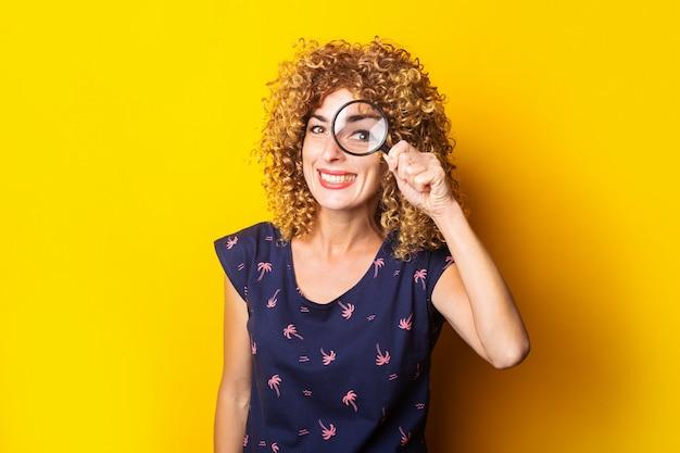 Веселая симпатичная кудрявая женщина смотрит в камеру через увеличительное стекло на желтой поверхности