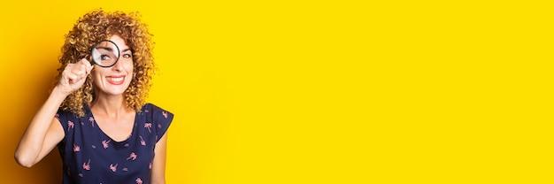 노란색 표면에 돋보기를 통해 카메라를보고 명랑 꽤 곱슬 여자