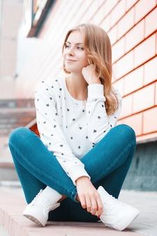 운동화 유행 청바지에 흰색 스웨터에 쾌활한 꽤 유럽 젊은 여자가 앉아 거리에 현대 벽돌 건물 근처에 꿈
