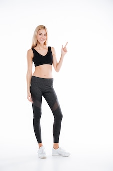 Cheerful pretty fitness lady pointing to copyspace