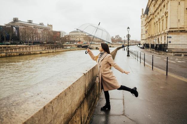 外を散歩する透明な傘を持っている陽気なかわいい女の子。