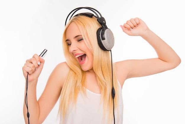 Веселая красивая девушка слушает музыку в наушниках и поет
