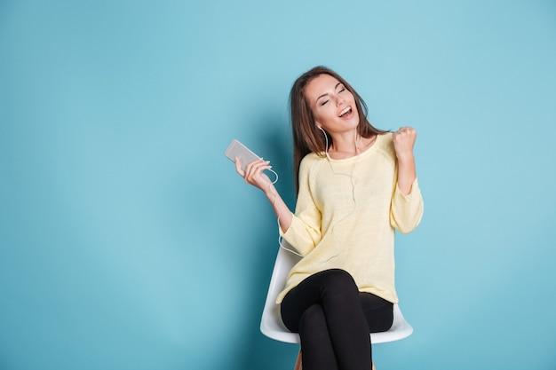 イヤホンで音楽を聴いて、青い背景で隔離の椅子に座っている陽気なかわいい女の子