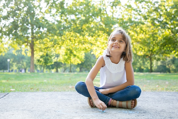 Cheerful pretty girl sitting and drawing with colorful pieces of chalks, looking away and smiling. front view. childhood and creativity concept