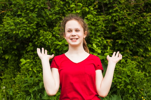 Cheerful pretty girl standing in park and gesturing