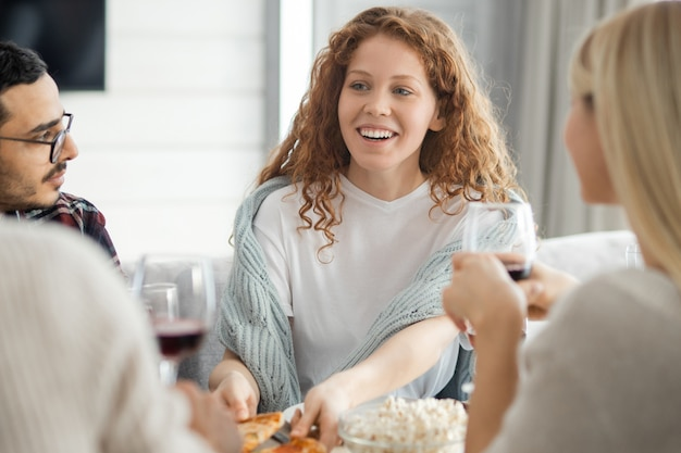 Веселая красивая девушка с вьющимися волосами берет кусок пиццы, делясь новостями с друзьями на сборе дома