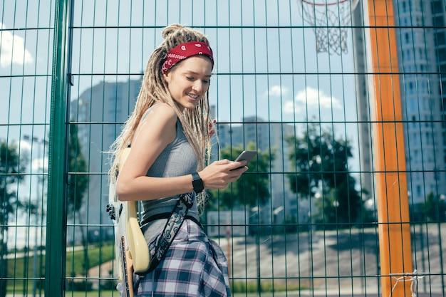 金網柵の隣に立って、彼女の現代のデバイスの画面を見ながら笑っている陽気なきれいな女性
