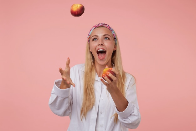 Cheerful pretty lady with long blond hair juggling with peaches, having fun, wearing colored headband and white shirt