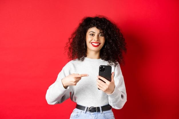 Bella signora allegra con lo smartphone che punta al telefono, sorridendo soddisfatto, consiglia un'app, in piedi su sfondo rosso