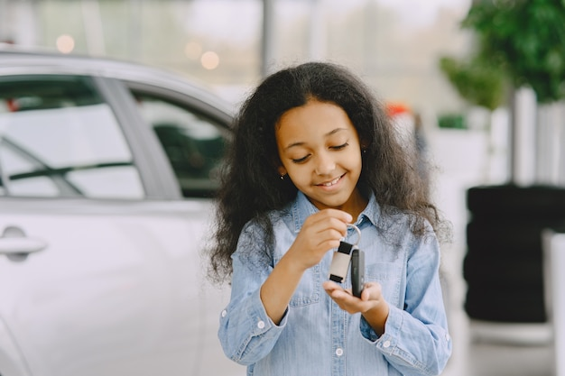 Bambina allegra e graziosa, che tiene le chiavi della macchina, lo mostra, sorride e posa.
