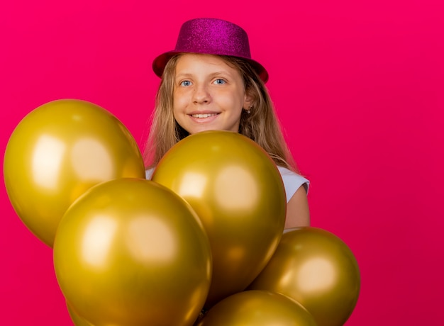 Cheerful pretty little girl in holiday hat with bunch of baloons looking at camera smiling with happy face, birthday party concept standing over pink background