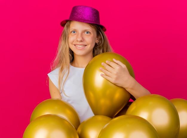 행복 한 얼굴로 웃 고 카메라를 찾고 baloons의 무리와 함께 휴가 모자에 쾌활 한 예쁜 소녀, 생일 파티 개념 분홍색 배경 위에 서