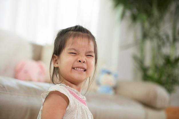 アパートのリビングルームに立っているときに笑顔と目を細めて陽気なかわいい女の子
