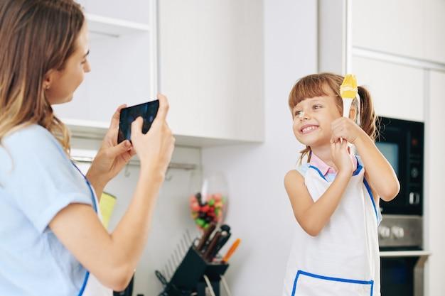母親がスマートフォンで写真を撮るときにシリコーンブラシでポーズをとって彼女の鼻に小麦粉を持つ陽気なかわいい女の子
