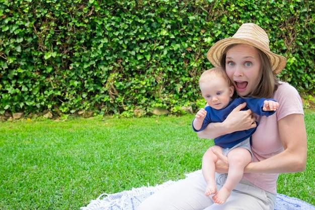 Mamma graziosa allegra che si siede sul plaid nel parco con la bocca aperta, che tiene neonato e che guarda l'obbiettivo. bambino sveglio in camicia blu sulle mani della madre