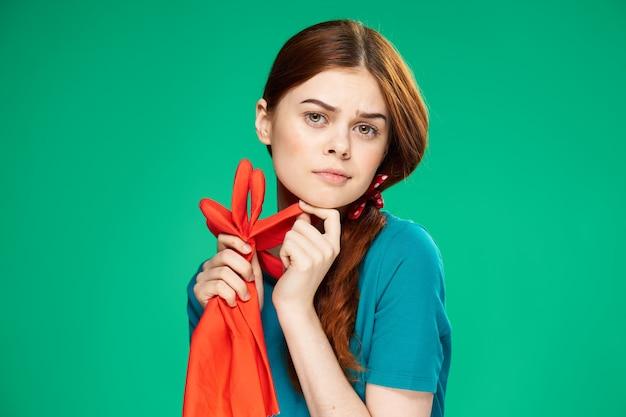 手に手袋をはめて家事を掃除する陽気なきれいな赤毛の女性