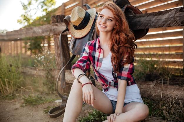 쾌활 한 예쁜 빨간 머리 젊은 여자 카우걸 앉아 야외에서 웃 고