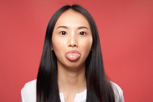 陽気なきれいな女性のアジアの外観の感情が魅力的な外観のクローズアップ赤い壁。