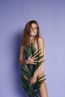 Cheerful pretty woman charm smile palm leaves. leaf of palm behind model. beautiful.