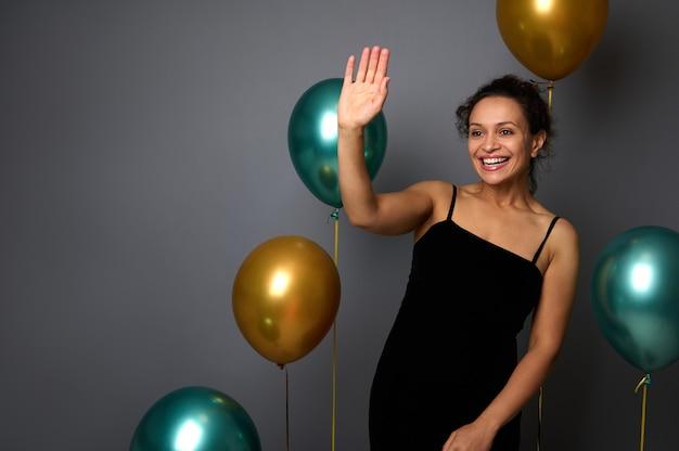 우아한 검은색 이브닝 드레스를 입은 쾌활한 예쁜 여성은 금색과 녹색 금속으로 부풀린 풍선, 손으로 파도 인사, 이빨 미소로 웃는 회색 벽 배경에 서 있습니다.
