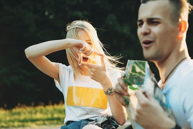 Веселая красивая женщина жестикулирует рамку и смотрит на парня на природе