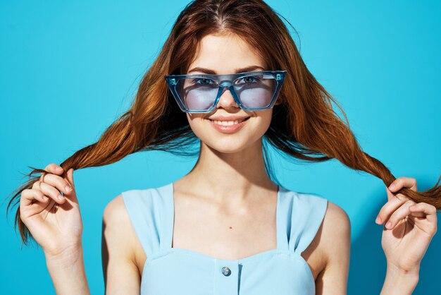 그녀의 머리에 의해 파란색 안경 드레스를 들고 명랑 예쁜 여자보기 스튜디오를 잘립니다.
