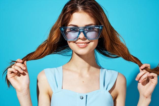 彼女の髪のトリミングされたビューで青いメガネのドレスを保持している陽気なきれいな女性