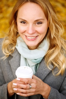 Cheerful pretty woman holding paper cup of coffee in autumn park looking at camera