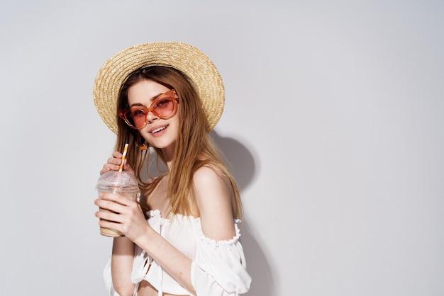 Веселая красивая женщина в розовой шляпе эмоций очки в стакане с роскошным напитком. фото высокого качества