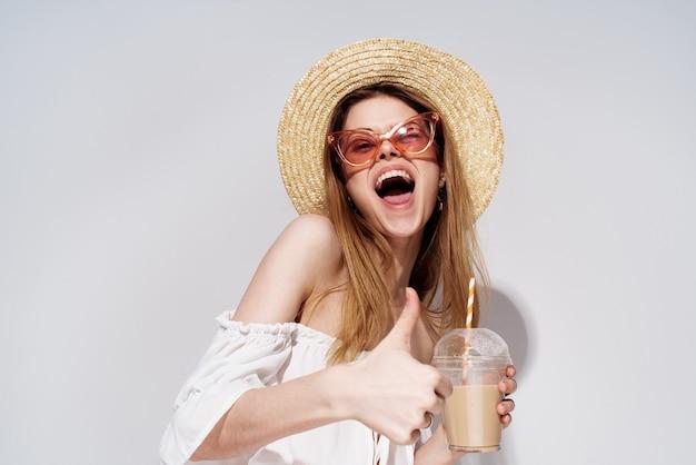 Веселая красивая женщина в розовой шляпе эмоций очки в стакане с роскошным напитком.