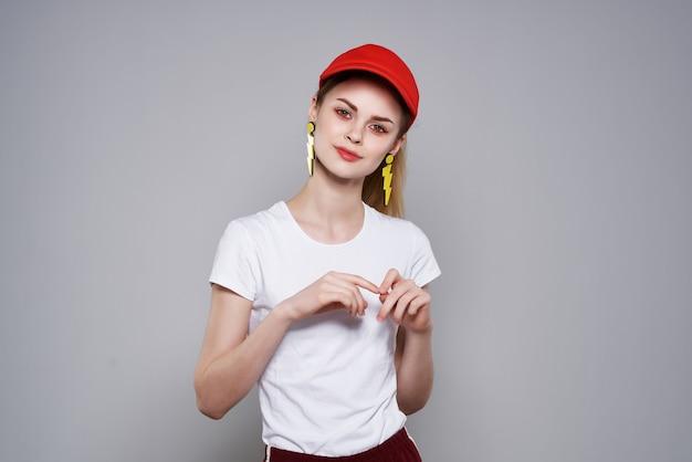 夏の黄色のイヤリングをポーズする赤い帽子の陽気なきれいな女性