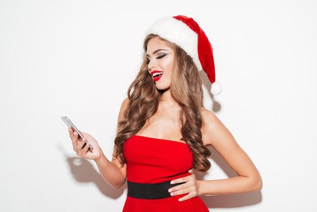 Веселая красивая женщина в красном платье и шляпе, используя мобильный телефон и глядя в сторону, изолирована