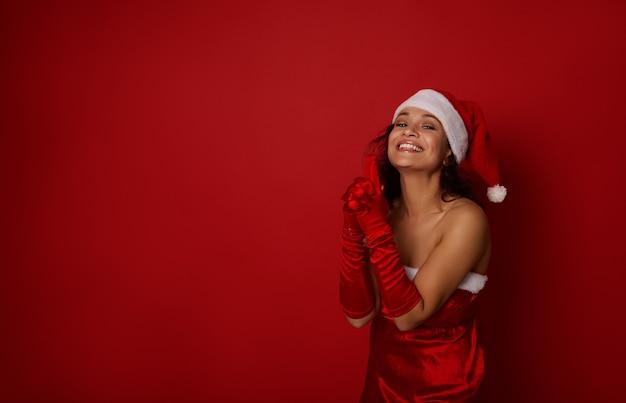 산타 카니발 의상을 입은 쾌활한 예쁜 여성이 손을 잡고 총을 쏘고 카메라를 보고 귀엽게 웃고 광고를 위한 복사 공간이 있는 빨간색 배경에 포즈를 취합니다. 새해와 크리스마스 휴일을 만나다