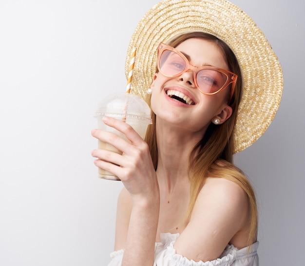 Веселая красивая женщина в летних очках шляпы пить развлечения. фото высокого качества
