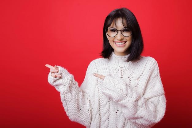 하얀 스웨터와 빨간색에 멀리 가리키는 안경에 쾌활 한 예쁜 여자
