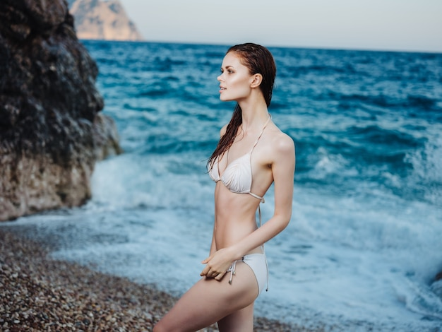 白い水着ファッションポーズで陽気なきれいな女性
