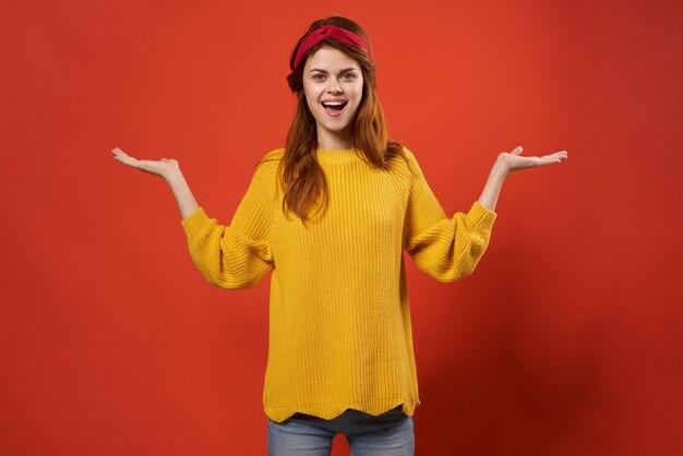 レトロな黄色のセーターモーダスタジオ装飾の陽気なきれいな女性。高品質の写真