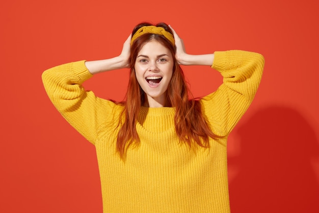 黄色いセーター赤い髪のヒッピーファッションの陽気なきれいな女性。高品質の写真