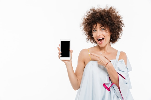 Cheerful pretty woman pointing finger at blank screen mobile phone