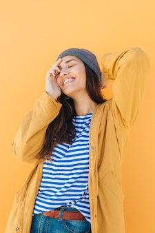 Cheerful pretty woman posing wearing knit hat with her eyes closed