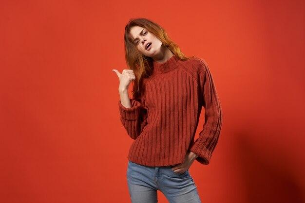 陽気なきれいな女性の赤い背景スタジオのクローズアップ