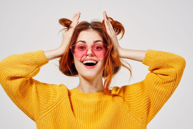 Веселая красивая женщина в розовых очках и держит ее волосы улыбкой желтый свитер крупным планом.