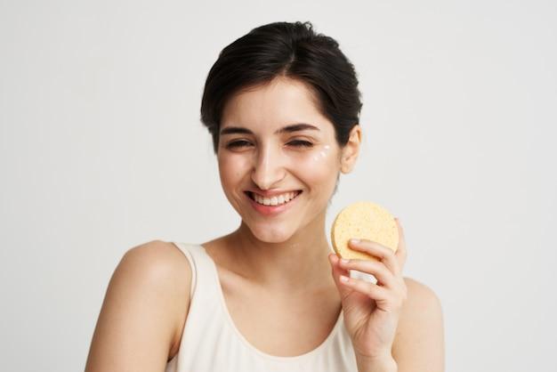 Веселая красивая женщина с губкой в руках косметика по уходу за кожей цветной фон светлый фон