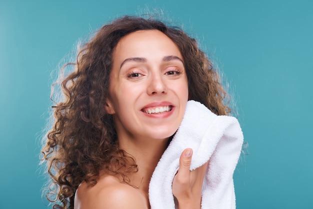 아침 위생 후 흰색 부드러운 면화 타월로 그녀의 얼굴을 건조하는 건강한 피부를 가진 쾌활한 예쁜 여자
