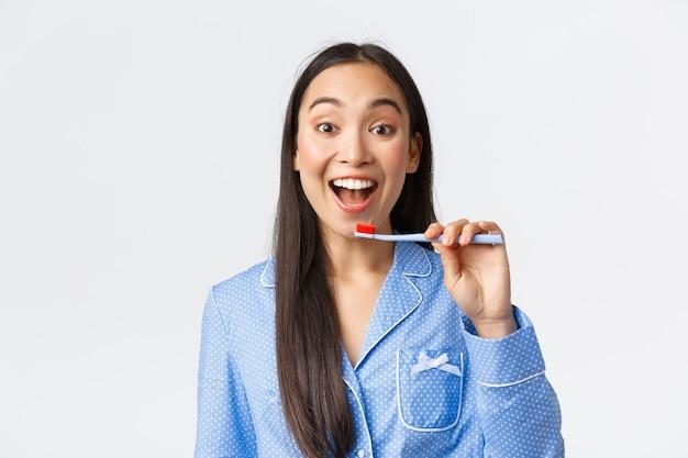 Веселая довольно молодая азиатская девушка в синей пижаме просыпается, чистит зубы с широкой восторженной улыбкой, держит зубную щетку возле белых зубов, на белом фоне. копировать пространство