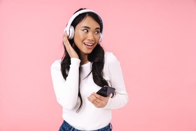 Веселая довольно молодая азиатская женщина слушает музыку с изолированными беспроводными наушниками, держа мобильный телефон